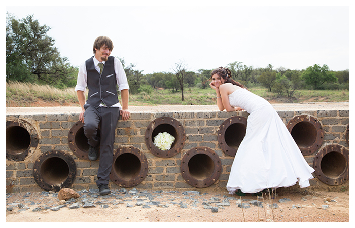 bride and groom next to old brick bridge