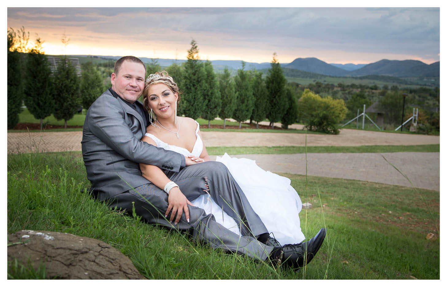 bride and groom with beautiful sunset and mountain range in background at La WiiDA Lodge