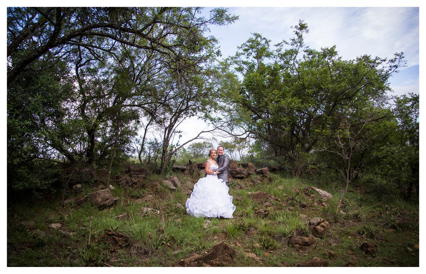 bride and groom on the rocks with blue sky and trees in background at La WiiDA Lodge