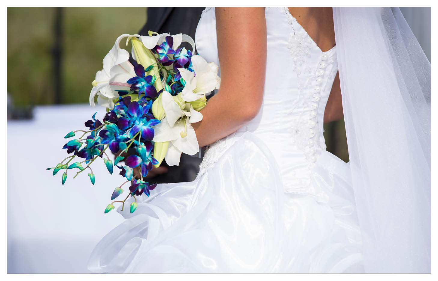 bride holding her magnificent white Lily and Blue Orchid  bouquet at La WiiDA Lodge