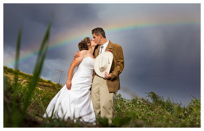 Clarens wedding photography - couple kissing with rainbow cowboy theme wedding at Lynwood Farm