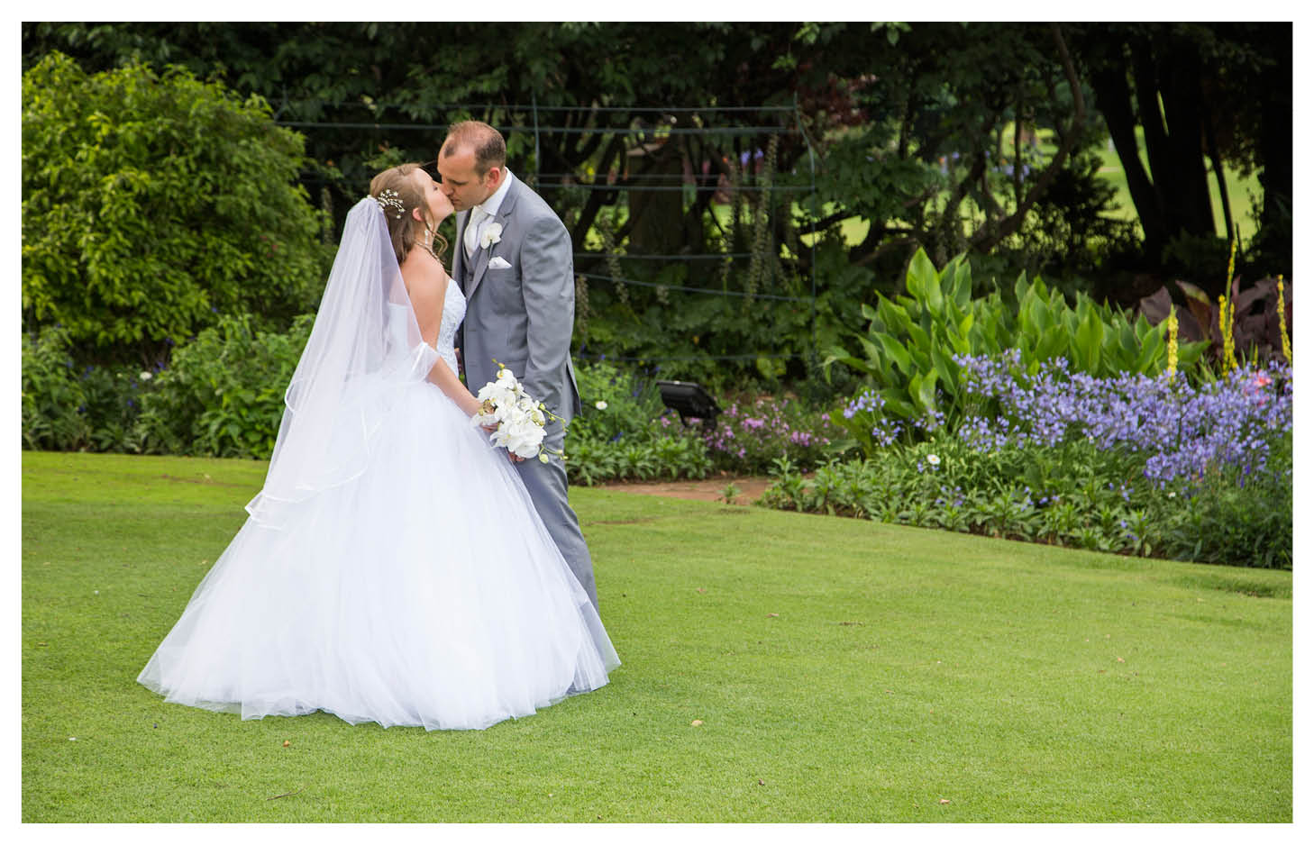 bride and groom kissing on perfect green grass at the country club johannesburg