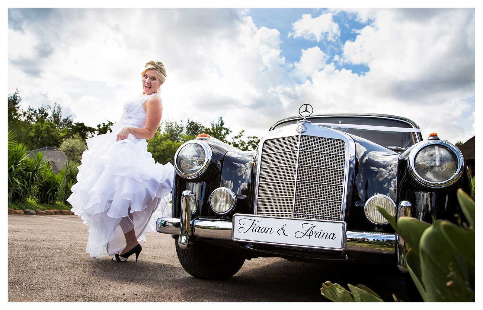 Excited bride with vintage car